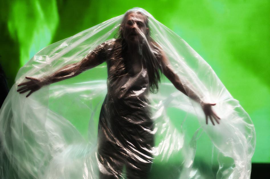actor under plastic sheet green background