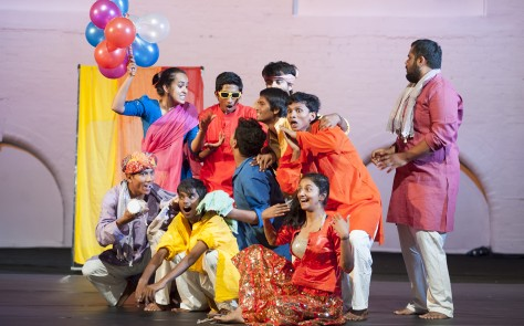 male and female cast dressed in bright colours and traditional Indian dress