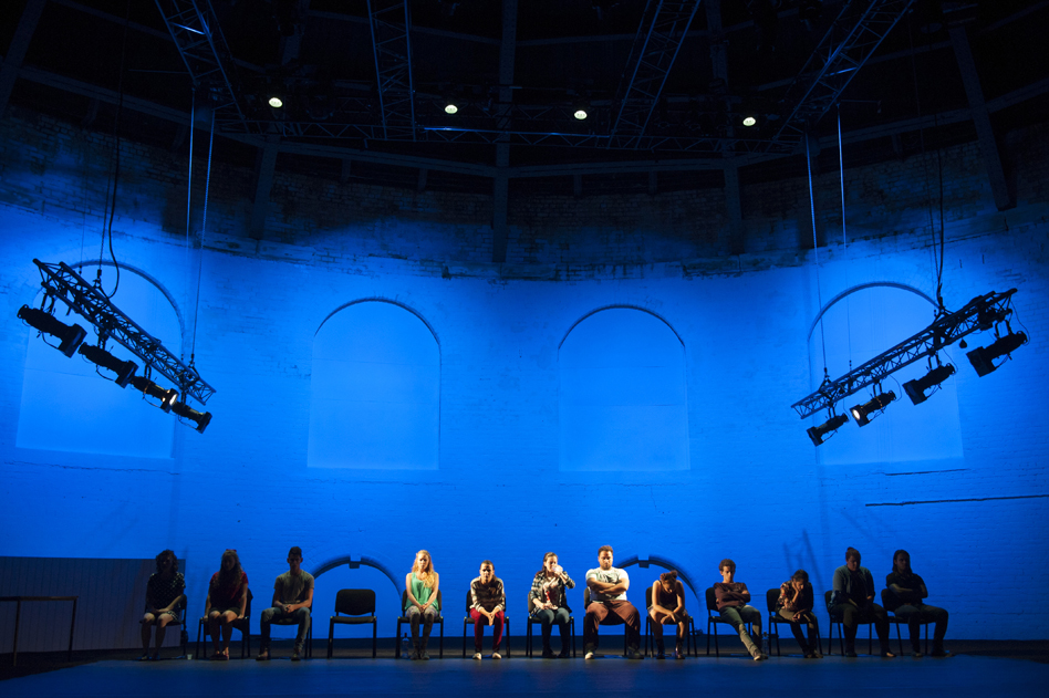actors on stage with a blue background