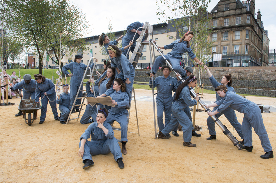 Performers in boiler suits on ladders