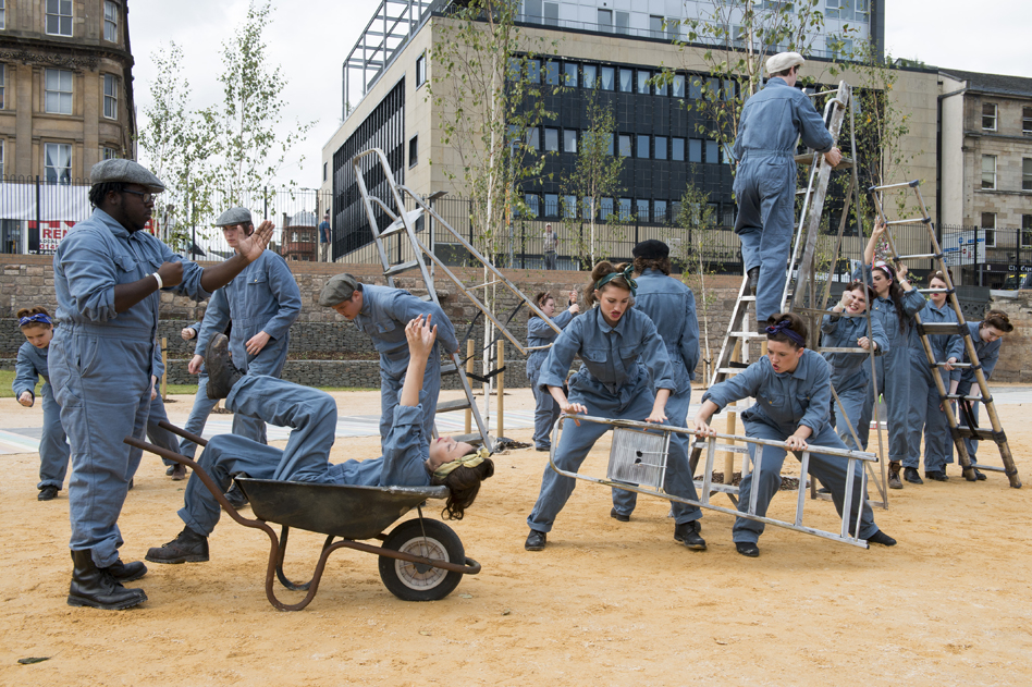 performers pushing wheelbarrows in the city