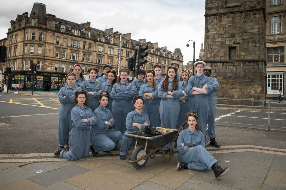 Performers dressed in blue boiler suits in a street in Glasgow