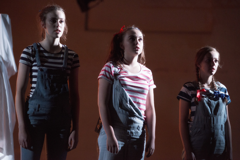 3 young female actors wearing dungarees and stripey tops